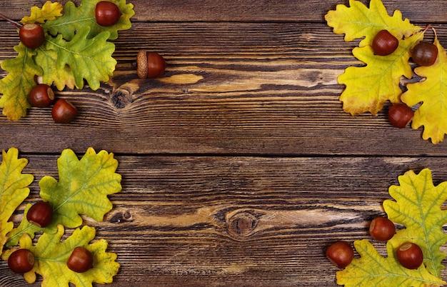 茶色の織り目加工の木材にドングリと黄色のオークの葉を使ったフラットレイの秋の構成