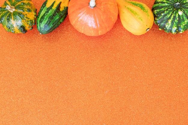 주황색 반짝이 배경에 장식용 호박의 복사 공간이 있는 평평한 가을 구성