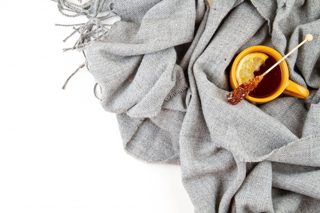 Flat lay autumn composition with cup of tea and a warm woolen scarf