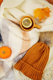 Flat lay autumn composition with fall leaves, hot cup of tea, scarf and a warm woolen orange hat