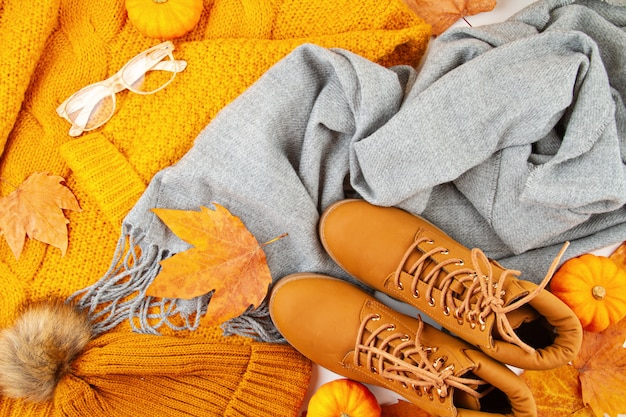 Flat lay autumn composition with fall leaves, pumpkins, boots and a warm woolen scarf and sweater