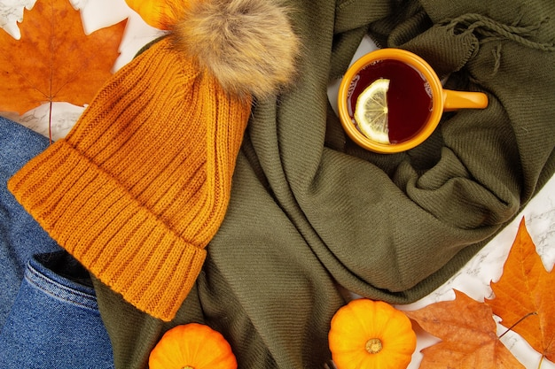 Flat lay autumn composition with fall leaves, pumpkins, hot cup of tea and a warm woolen scarf and hat
