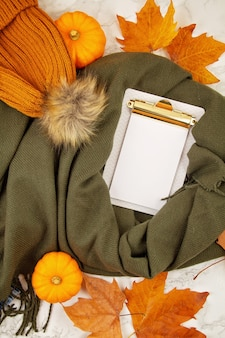 Flat lay autumn composition with fall leaves, pumpkins, jeans and a warm woolen scarf and hat