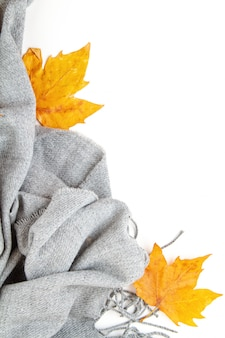 Flat lay autumn composition with leaves and a warm woolen scarf