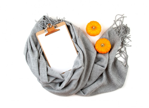 Flat lay autumn composition with notepad and a warm woolen scarf