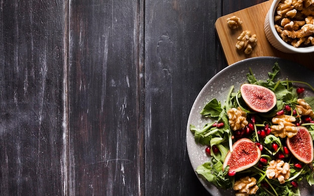 Flat lay of autumn fig salad on plate with walnuts and copy space