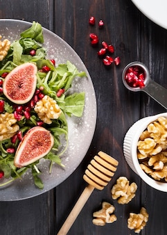Flat lay of autumn fig salad on plate with walnuts