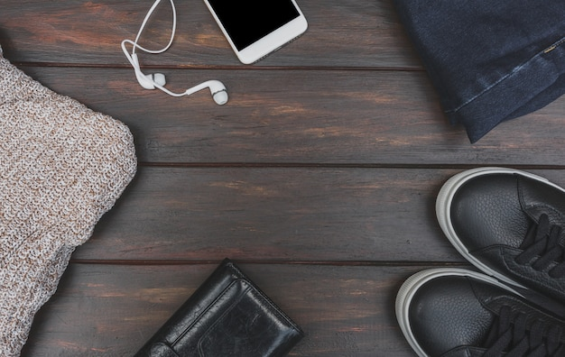 Flat lay of autumn or winter cloth and accessory on wooden table with copy space. woolen sweater, phone with headphones, blue jeans, leather sneakers and purse