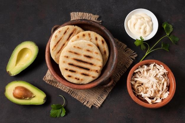Disposizione piatta di avocado e arepas