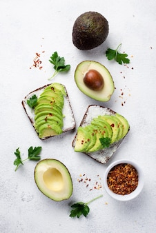 Flat lay of avocado toast for breakfast with herbs and spices