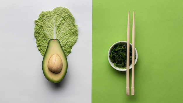 Flat lay of avocado with bowl of greens and chopsticks