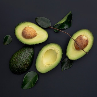 Flat lay of avocado with pit and leaves