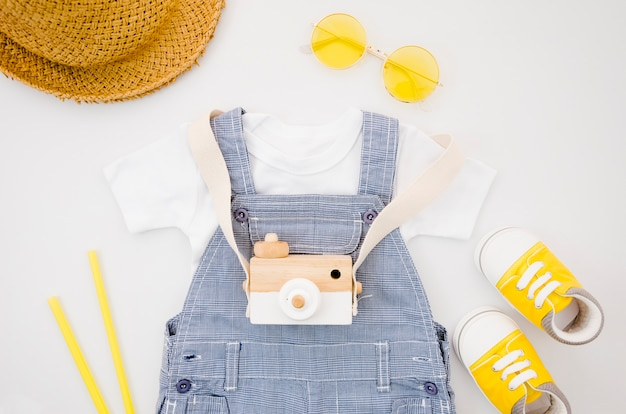 Flat lay baby clothes with photo camera