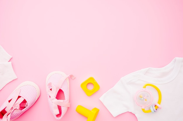 Flat lay baby clothes with pink background