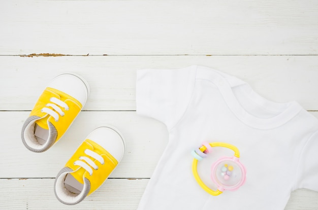 Flat lay baby clothes with wooden background