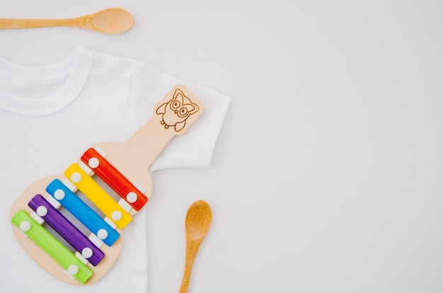Flat lay baby clothes with xylophone