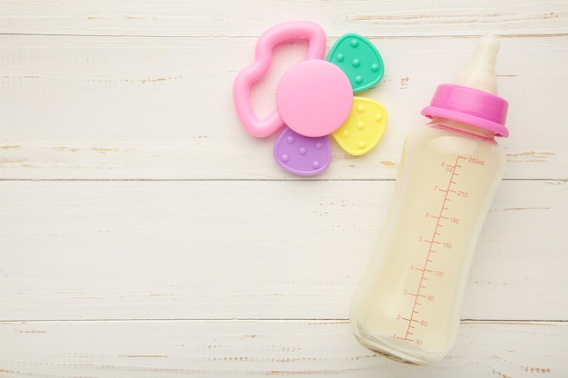 Flat lay of baby milk with toys on white background