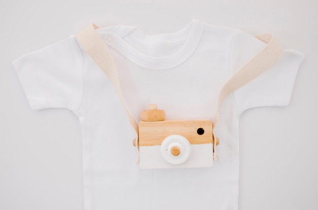 Flat lay baby t-shirt with photo camera