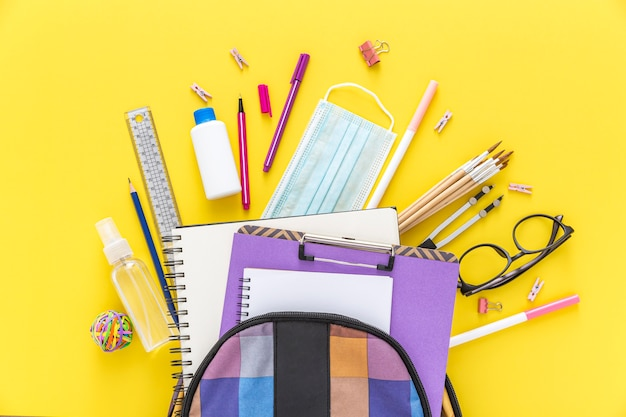 Flat lay of back to school materials with book bag and glasses
