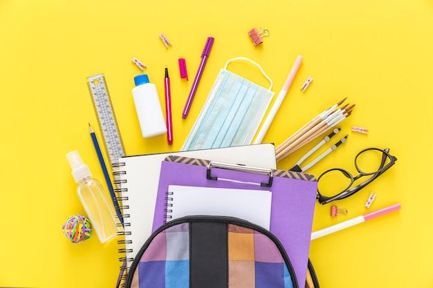 Distesa piatta di materiale scolastico con borsa per libri e occhiali