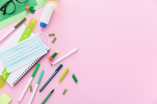Flat lay of back to school materials with face masks and pencils