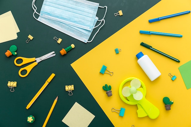 Flat lay of back to school materials with scissors and face masks