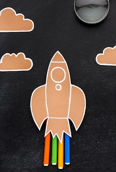 Flat lay of back to school rocket with pencils and clouds