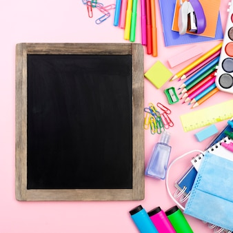 Flat lay of back to school stationery with blackboard and medical mask