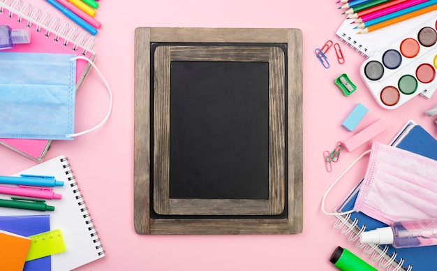 Flat lay of back to school stationery with blackboard and multicolored pencils