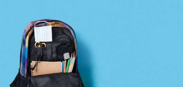 Flat lay of back to school supplies in book bag with copy space