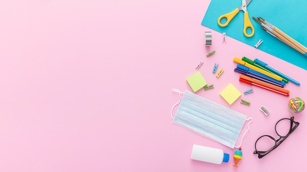 Flat lay of back to school supplies with glasses and pencils