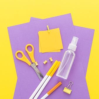 Distesa piatta di materiale scolastico con disinfettante per le mani e forbici
