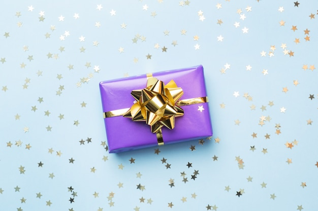 Flat lay background for celebration christmas and new year. gift boxes are purple with gold ribbons bows and confetti stars on a blue background. top view copy space.