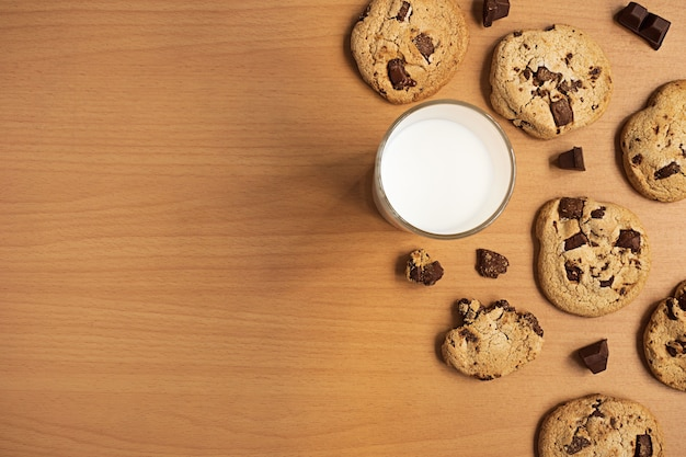 Flat lay background of chocolate cookies and chocolate bar and a cup of milk
