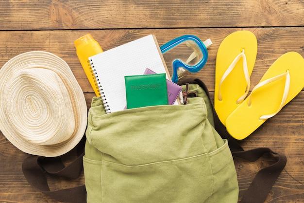 木製の旅行の概念に空白のノートブックと旅行者のアクセサリーとフラットレイアウトバックパック