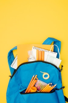 Flat lay backpack with school supplies