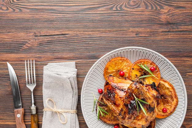 Плоские лежал запеченный цыпленок и дольки апельсина на тарелке со столовыми приборами и салфеткой