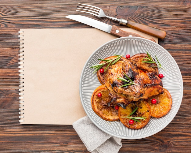 Flat lay baked chicken and orange slices on plate with cutlery and blank notebook