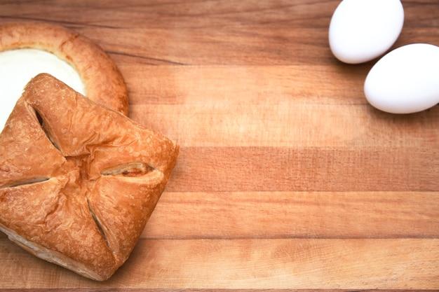 Плоская планировка. выпечка или приготовление пищи. кухонная утварь, ингредиенты для выпечки тортов и пирогов, яйца, пирог с начинкой, чизкейк. текстовое пространство, вид сверху.