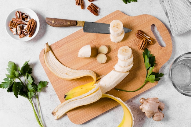 Flat lay of banana on chopping board with ginger
