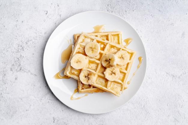 Flat lay of banana slices and honey on waffles