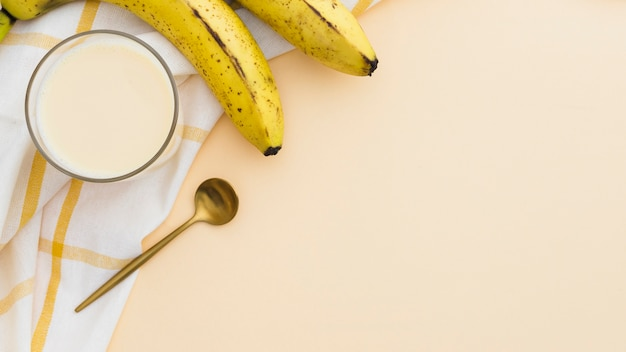 Flat lay of banana smoothie with golden spoon
