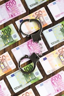 手錠と木製のテーブルの上の平らなレイアウト紙幣