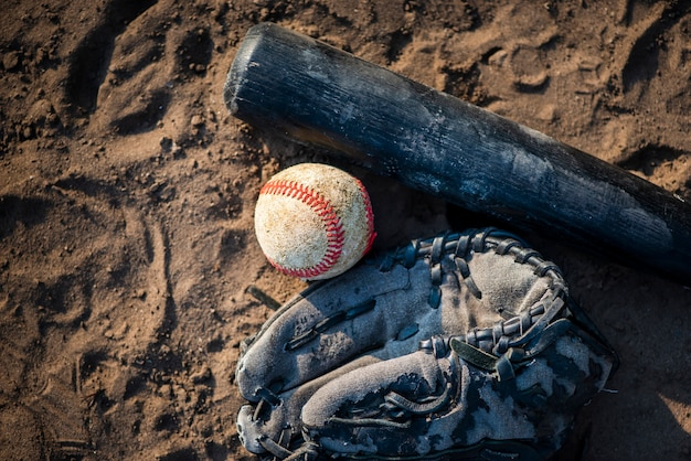 Flat lay of baseball and bat in dirt