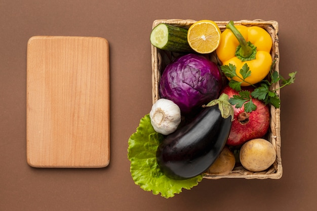 Flat lay of basket of fresh vegetables with chopping board