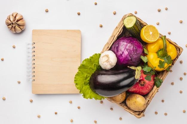 Lay piatto del cesto di verdure fresche con il taccuino
