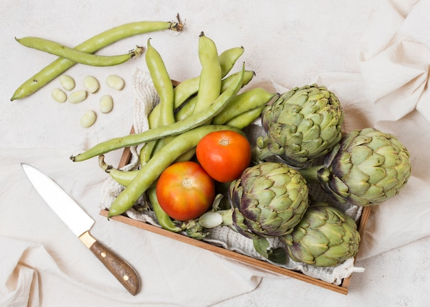 Flat lay of basket with artichokes and tomatoes