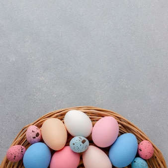 Flat lay of basket with colorful easter eggs and copy space
