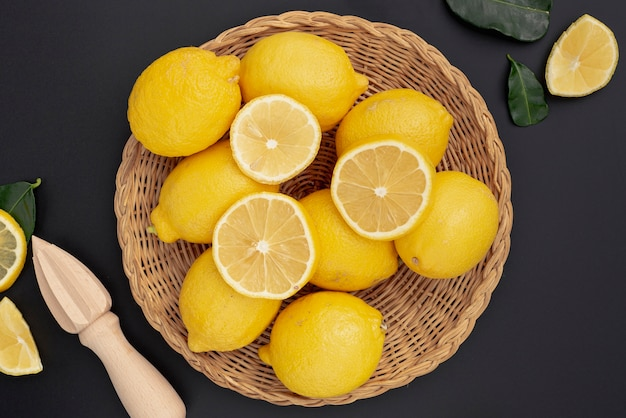 Flat lay of basket with lemons and squeezer