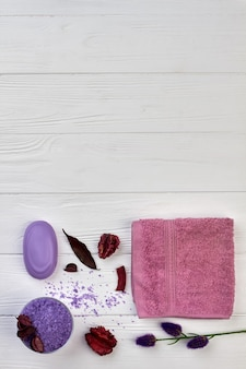 Flat lay bath spa accessories on white wooden desk.